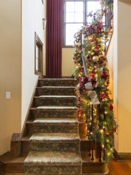 ImagesBanister decorated with boughs and string lights for Christmas