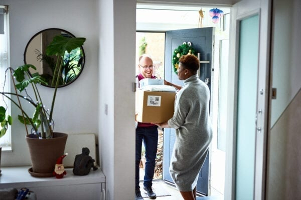 Woman receiving delivery from courier at front door, Christmas wreath, Christmas shopping, convenience