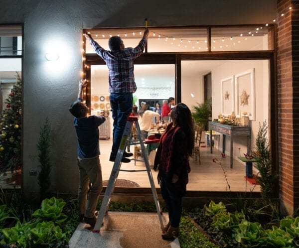Happy Latin American family decorating the house for Christmas and hanging lights on the door - lifestyle concepts
