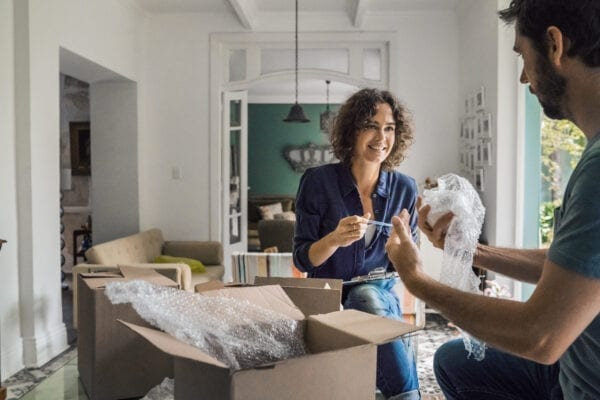 A photo of happy young couple are packing boxes. Woman is looking at male partner. They are moving in new house.
