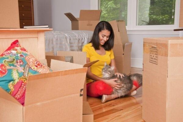 Hispanic woman sitting on floor petting cat near moving boxes