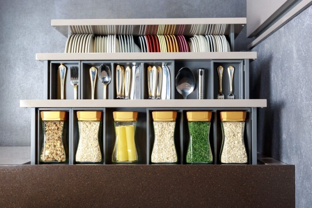 Open kitchen drawers with well organized food, silverware, and dishes