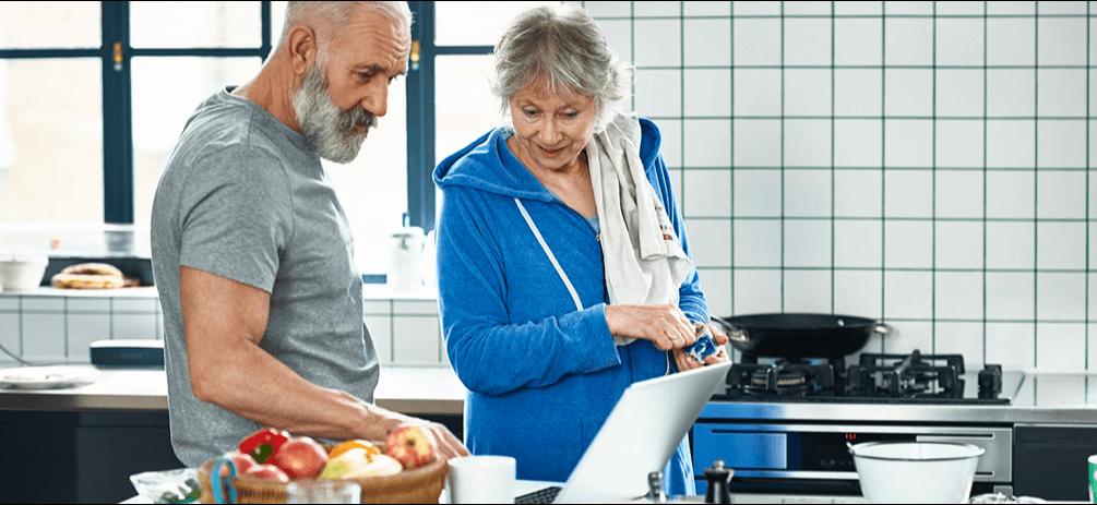 senior couple in kitchen on computer