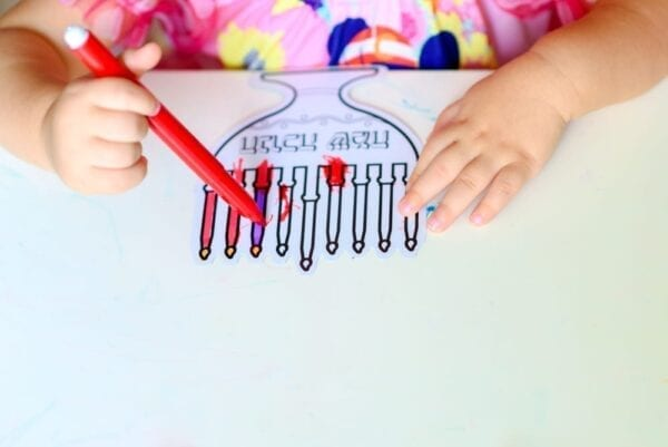 Close up hand cute little toddler kid painting with color pen paper menorah and candle Jewish holiday Chanukah.