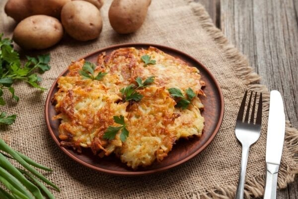 Homemade traditional potato pancakes or latke Hanukkah celebration food in rustic clay dish on vintage wooden background.
