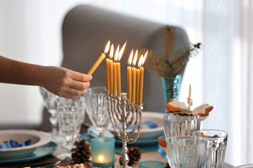 Female hand lighting candles in menorah on table served for Hanukkah