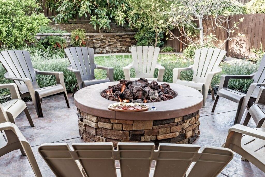 Backyard fire pit surrounded by Adirondack chairs