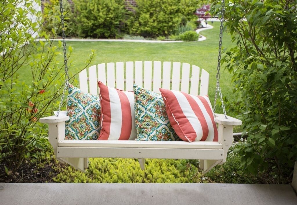 White porch swing with pillows in front yard