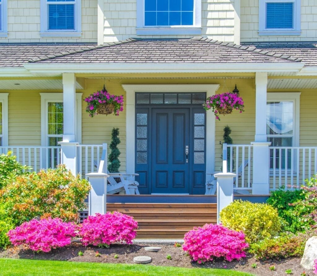 Entrance to house with beautiful landscaping and flowers