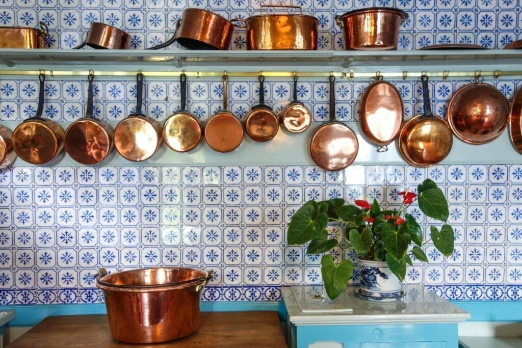 Kitchen with blue tile backsplash and copper pots and pans
