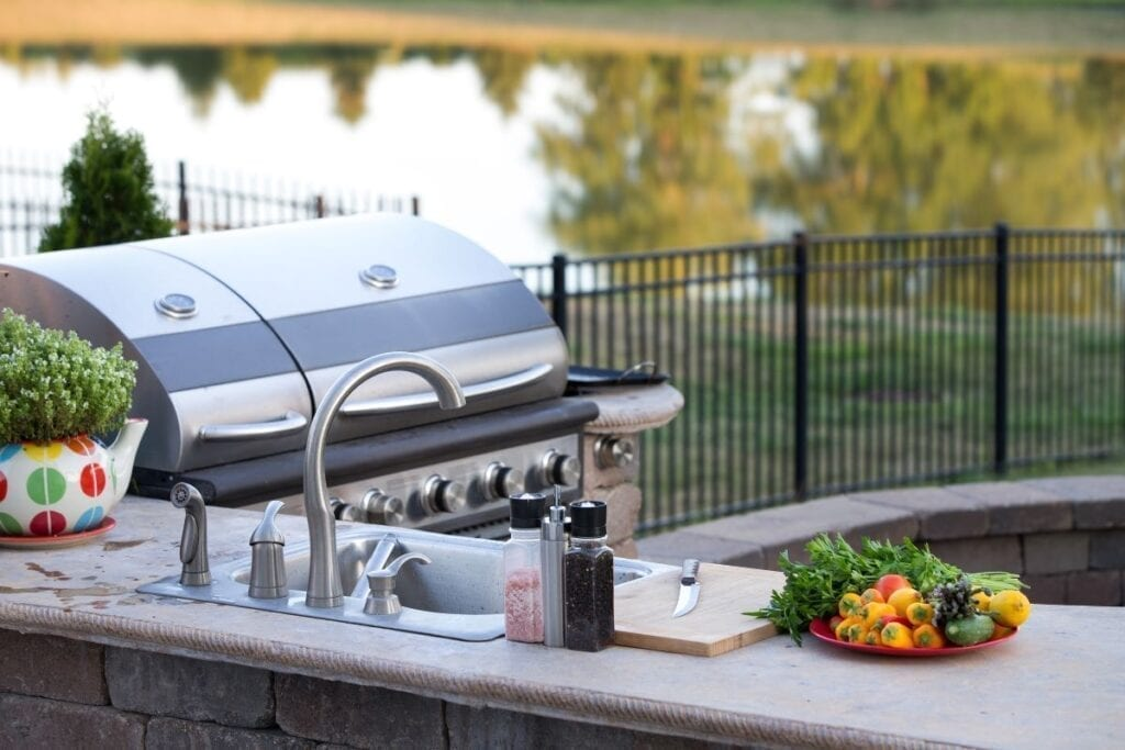 Outdoor kitchen with sink and grill in back yard