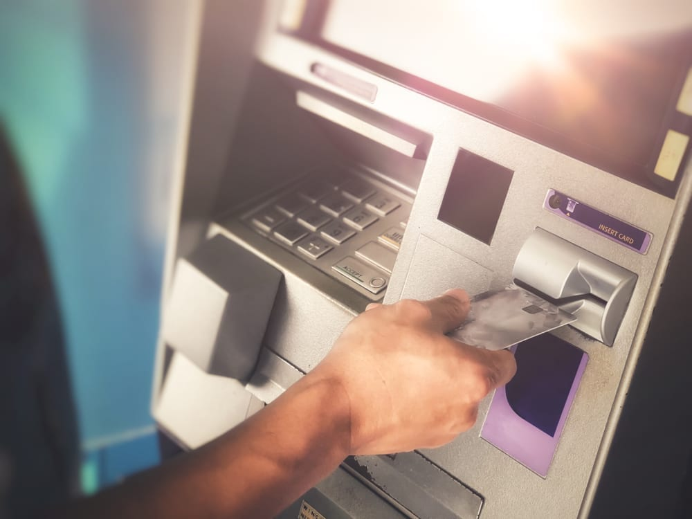 Close up of hand inserting debit card into ATM machine.