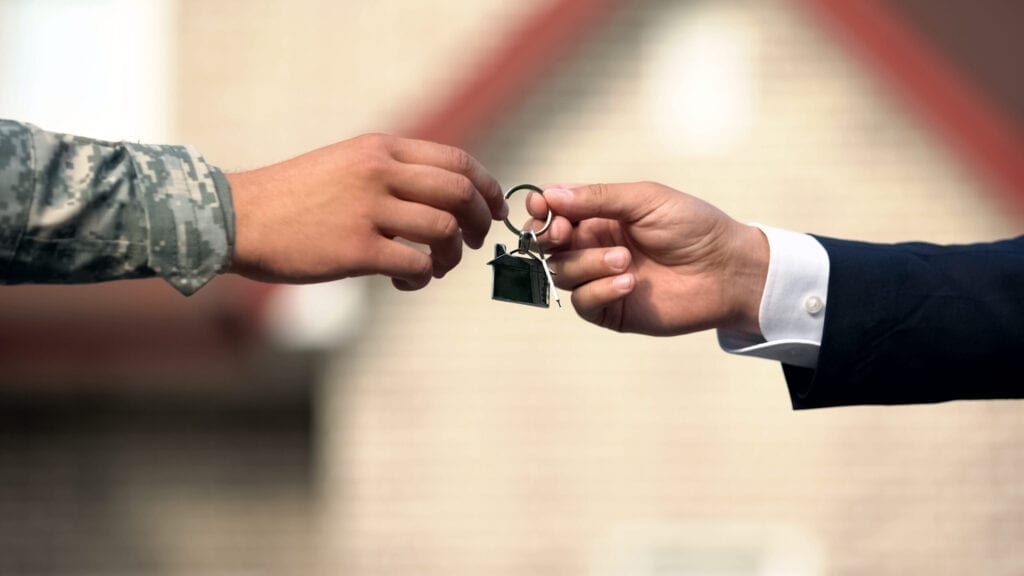 Man in business suit giving house key to man in military uniform, state support