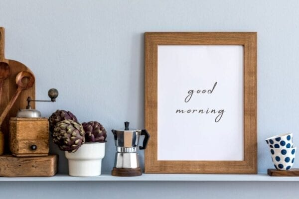Kitchen shelf decorated with photo frame, wooden cutting board, coffee maker, and cups