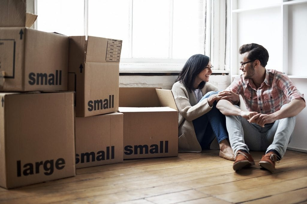 Couple is planning their move and sitting next to packed boxes. Free moving quotes help them hire moving companies.